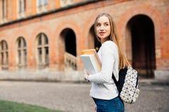 Smart kvinnlig högskolestudent med påsen och böcker på universitetsområde utomhus royaltyfri foto