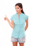 Smart lady looking at you with thumb up. Gesturing ok sign while standing in white background Stock Photography