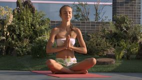 Lady Meditates in Lotus Pose by Tropical Plants. Smart lady in open white clothes meditates in lotus pose against tropical pot plants on roof terrace stock footage
