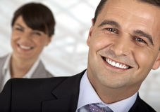 Smart leader. Close-up of a male smiling in front of a female stock image