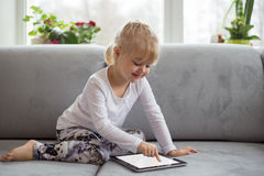 Smart liten flicka som använder minnestavladatoren, medan sitta på soffan i vardagsrum hemma Royaltyfria Foton
