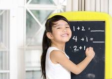 Smart liten flicka som framme ler av en svart tavla Arkivbild