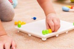Smart liten flicka som leker med mosaiken Arkivfoton
