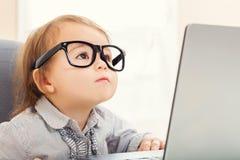 Smart litet barnflicka som bär stora exponeringsglas, medan genom att använda hennes bärbar dator Royaltyfri Fotografi