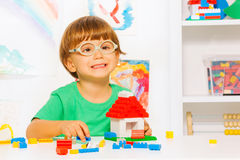 Smart little boy build toy plastic blocks house Stock Photo