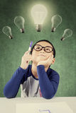 Smart little boy holding a pen under light bulb Royalty Free Stock Photography