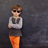Smart little boy standing against blackboard Royalty Free Stock Photos