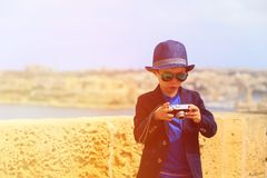 Smart little boy taking photos while travel in Stock Photography