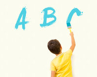 Smart little boy writing ABC Stock Images