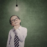Smart little businessman under lit bulb Royalty Free Stock Images