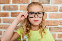 Smart little girl in glasses with black frames Royalty Free Stock Images