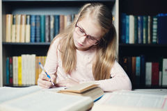 Smart little girl with glasses writing on book, Stock Images