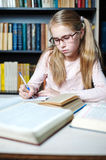 Smart little girl with glasses writing on book, Royalty Free Stock Photography