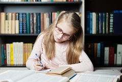 Smart little girl with glasses writing on book, stock image