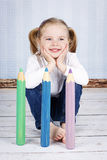 Smart little girl holding  big crayons Stock Images