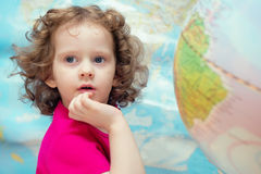 Smart little girl looks closely, the picture on the background o Royalty Free Stock Images