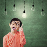 Smart little girl pointing at lamp. Portrait of attractive female student pointing at bright lamp in the class while wearing glasses Royalty Free Stock Photography