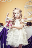 Smart little girl posing in cozy decorated studio Stock Photography