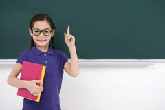 Smart little girl. Pretty little schoolgirl holding her finger u Royalty Free Stock Photos