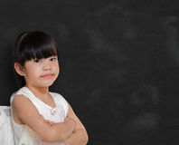 Smart little girl smiling in front of a blackboard. Stock Image