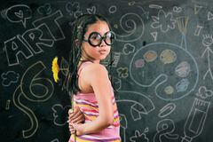 Smart little girl smiling in front of a blackboard Stock Photography