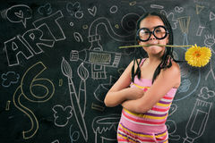 Smart little girl smiling in front of a blackboard Royalty Free Stock Images