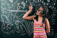 Smart little girl smiling in front of a blackboard Stock Photo