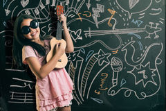 Smart little girl smiling in front of a blackboard Royalty Free Stock Photography