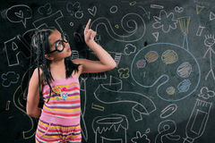 Smart little girl smiling in front of a blackboard Royalty Free Stock Photo