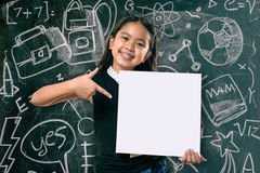 Smart little girl smiling in front of a blackboard Royalty Free Stock Photos