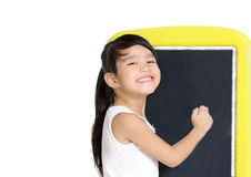 Smart little girl smiling in front of a blackboard  on white background. Royalty Free Stock Image