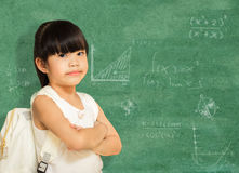 Smart little girl  successful standing in front of a blackboard. Stock Images