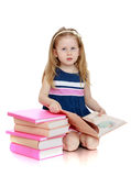 Smart little girl too young to attend school sits Royalty Free Stock Photos