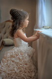 Smart little girl in white dress. By the window royalty free stock image