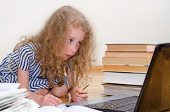 Smart little girl writes diploma. stock photos