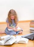 Smart little girl writes diploma. Royalty Free Stock Photo