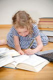 Smart little girl writes diploma. royalty free stock image