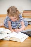 Smart little girl writes diploma. Royalty Free Stock Image