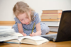 Smart little girl writes diploma. royalty free stock photography