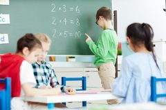 Math lesson in elementary school. Smart little schoolboy standing by blackboard in classroom and doing multiplication sums on math class Royalty Free Stock Photos