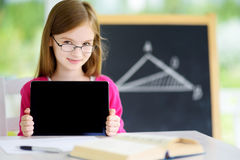 Smart little schoolgirl with digital tablet in a classroom Royalty Free Stock Photography