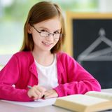 Smart little schoolgirl with pen and books writing a test in a classroom Royalty Free Stock Photography