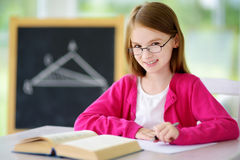 Smart little schoolgirl with pen and books writing a test in a classroom Stock Image
