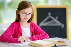 Smart little schoolgirl with pen and books writing a test in a classroom. Child in an elementary school. Education and learning for kids Royalty Free Stock Photo