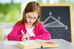 Smart little schoolgirl with pen and books writing a test in a classroom. Child in an elementary school. Royalty Free Stock Images