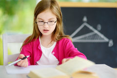 Smart little schoolgirl with pen and books writing a test in a classroom. Child in an elementary school. Royalty Free Stock Photography