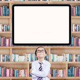 Smart little student looking up at whiteboard. Male little student thinking idea in the library while looking up at the empty board Royalty Free Stock Images