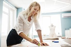 A smart-looking blond woman is lining a sewing cutting-out with a piece of soap. Fasion, tailor`s workshop. stock photos