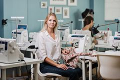 A smart-looking pretty blond woman wearing white shirt is sewing with the electric sewing-machine. Fashion, tailor`s royalty free stock photo