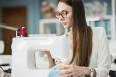 A smart-looking pretty brunet woman wearing white shirt is sewing with the electric sewing-machine. Fashion, tailor`s stock photo
